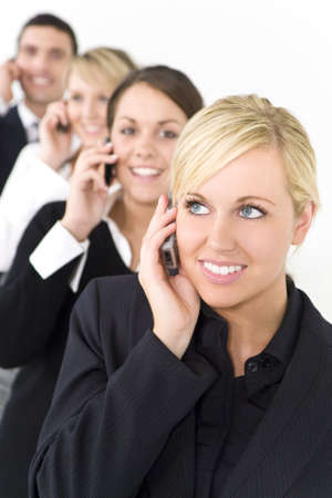 A businesswoman with three other executives out of focus behind her all talking on cell phones photo