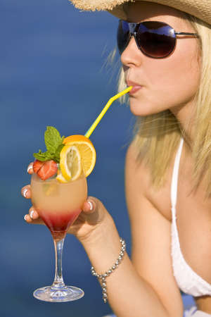 beach blond hair: Stunningly beautiful young blond woman in straw cowboy hat and sunglasses enjoying a cocktail by a deep blue sea