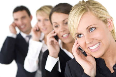 A businesswoman and her three colleagues out of focus behind her all talking on cell phones photo