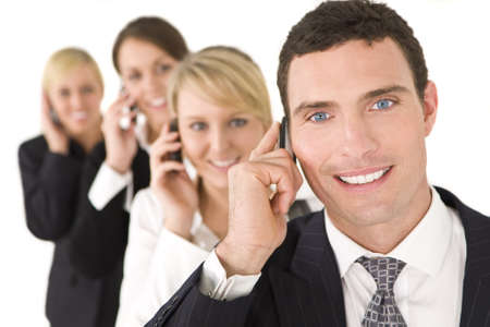 A businessman and three businesswomen out of focus behind him all talking on cell phones photo