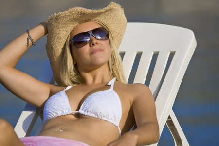 A beautiful young blond woman in sunglasses and cowboy hat relaxes in the sun by the sea Stock Photo
