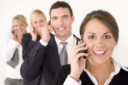 business woman phone: A businesswoman and three colleagues out of focus behind her all talking on cell phones Stock Photo