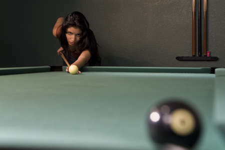 eight ball: A sexy and beautiful hispanic woman playing pool and about to sink the eight ball Stock Photo