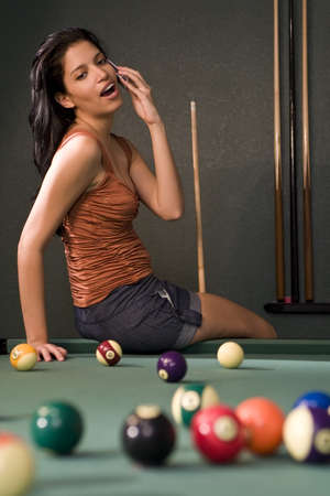 cue: A sexy and beautiful hispanic woman playing pool and chatting on her cell phone Stock Photo