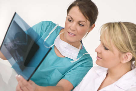 A female doctor and her nursing colleague examining an X-ray of a human skull Stock Photo - 4087409