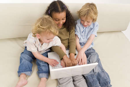 settee: Three young children using a laptop together while sitting on a settee
