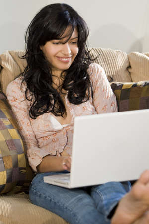 settee: A stunningly beautiful young Hispanic woman sitting on a settee having fun on her laptop