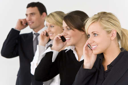 A businesswoman and three of her colleagues out of focus behind her all talking on cell phones photo