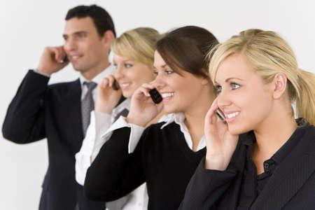 mobiele telefoons: Een zakenvrouw en drie van haar collega's van de focus achter haar alle praten over mobiele telefoons