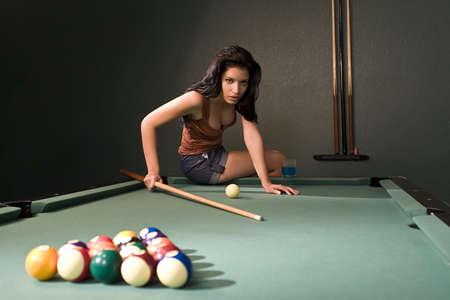 A sexy and beautiful hispanic woman playing pool  photo