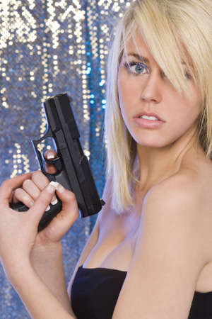 A stunningly beautiful young blond woman holding a handgun