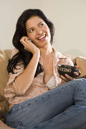 A beautiful young hispanic woman relaxing with a mug of cappuccino and chatting on her mobile phone Stock Photo - 4130245