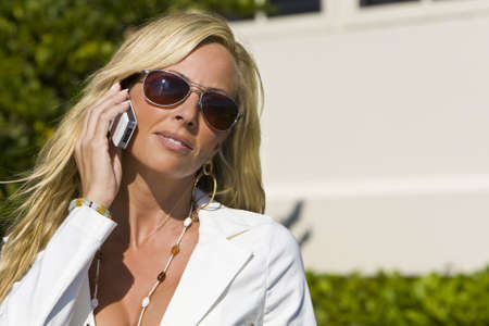 A beautiful young blond woman on the phone in a sunny location, shot with copy space Stock Photo - 4136501