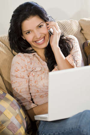 A stunningly beautiful young Hispanic woman sitting on a settee having fun on her laptop and chatting on her cell phone photo
