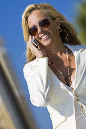 A beautiful young blond woman on the phone in a sunny location backed by high rise buildings and palm trees photo