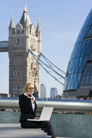 cell phone tower: A beautiful young female executive using her laptop and mobile phone in front of Tower Bridge, Canary Wharf and the London city skyline Stock Photo