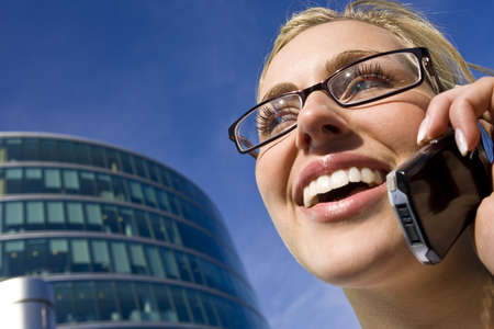 A beautiful young female executive using her cell phone in front a modern city building Stock Photo - 4153687
