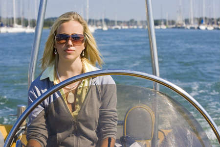A stunningly beautiful young woman driving a powerboat on a sunny summer day. photo