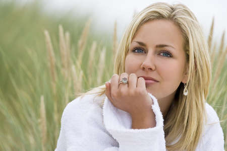 blonde blue eyes: A beautiful blond haired blue eyed model wearing a white towelling robe sits amid tall grass