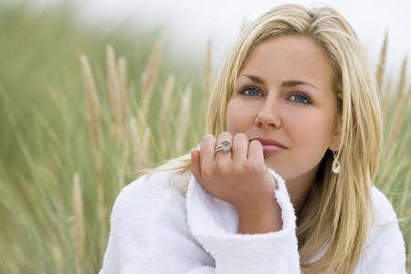 rubia ojos azules: Una bella rubia de ojos azules pelo modelo lleva un vestido blanco toallas se sienta en medio de hierba alta Foto de archivo