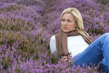 A beautiful blond haired blue eyed model laying down among purple heather photo