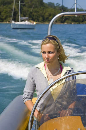 A stunningly beautiful young woman driving a powerboat away from her yacht at anchor off a Mediterranean coastline photo
