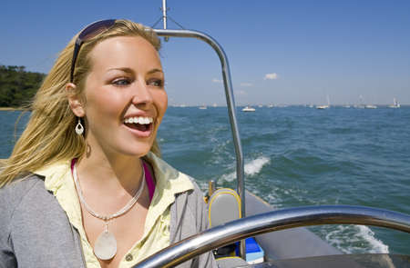 A stunningly beautiful young woman driving a powerboat and having fun in a beautiful sun drenched coastal location.