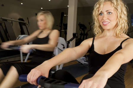 Two beautiful young women using rowing machines at the gym. The girl in the background is shown moving using in-camera motion blur. photo