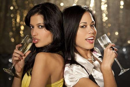 Two beautiful young women enjoying champagne in a nightclub photo