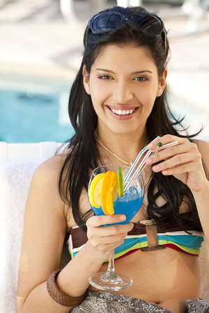 A stunningly beautiful young hispanic woman looking drinking a cocktail next to a swimming pool photo