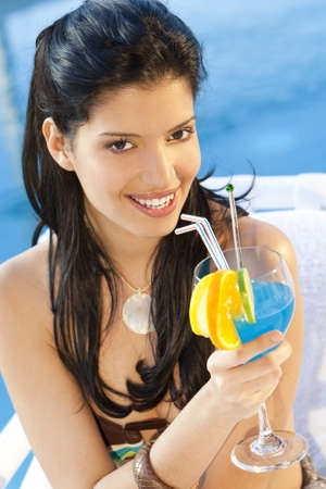 A stunningly beautiful young hispanic woman looking drinking a cocktail next to a swimming pool Stock Photo - 4193018