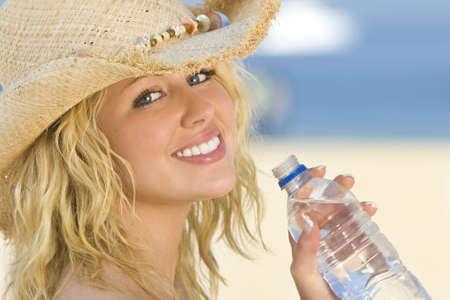 bionda occhi azzurri: Una sexy e giovane e bella donna bionda seduta sulla spiaggia a bere una bottiglia di acqua con la sabbia dorata e mare dietro di lei