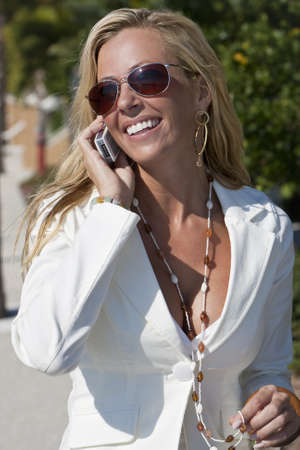 A beautiful young blond woman on the phone in a sunny location  Stock Photo - 4208142