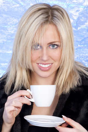 Studio shot of a stunningly beautiful young blonde woman drinking a cup of tea or coffee shot i a studio with an electric blue background photo