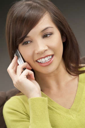 A beautiful young oriental woman with a wonderful smile chatting on her cell phone. Stock Photo - 4258094