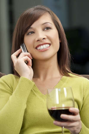 A beautiful young oriental woman with a wonderful toothy smile drinking red wine and chatting on her cell phone. Stock Photo - 4258095
