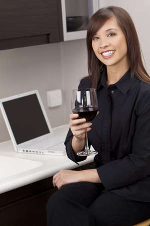 A beautiful young oriental woman with a wonderful toothy smile drinking red wine and using a laptop in her kitchen. photo