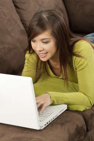 A beautiful young oriental woman with a wonderful laying down on her settee and using a laptop  photo