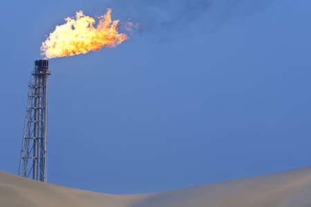 torres petroleras: Una pila de bengala quema el exceso de gas en una refiner�a de petr�leo en el desierto Foto de archivo