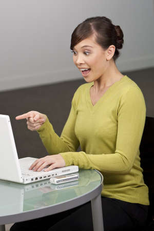 A beautiful young oriental woman using a laptop in her office looking happily surprised photo