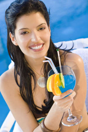 A stunningly beautiful young hispanic woman looking drinking a cocktail next to a swimming pool Stock Photo - 4303849