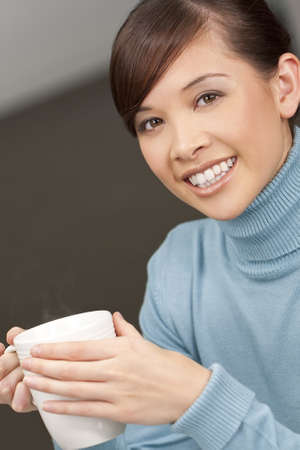 A beautiful young oriental woman with a wonderful toothy smile drinking a hot steaming drink from a white mug photo