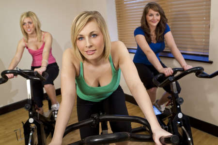 Three beautiful young women working out on spinning bikes at the gym photo
