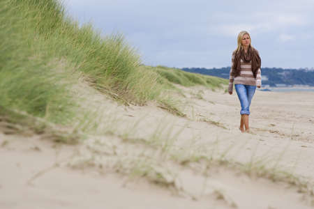 A beautiful young blond woman walking alone along a deserted beach Stock Photo