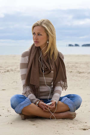 legged: A beautiful blond young woman sitting cross legged on a beach listening to her mp3 player with the sea behind her