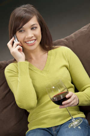 A beautiful young oriental woman with a wonderful toothy smile drinking red wine and chatting on her cell phone. Stock Photo - 4339527