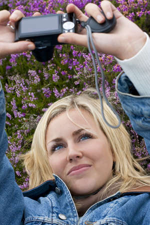 A beautiful blond haired blue eyed young woman laying down in a field of heather and taking a self portrait on her point and shoot digital camera photo