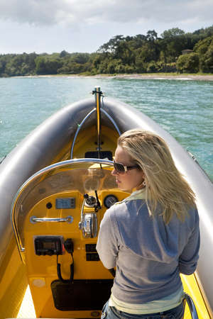 A stunningly beautiful young woman driving a powerboat and having fun. Stock Photo - 4339445