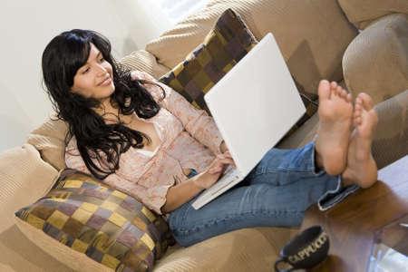 settee: A stunningly beautiful young Hispanic woman sitting on a settee having fun on her laptop