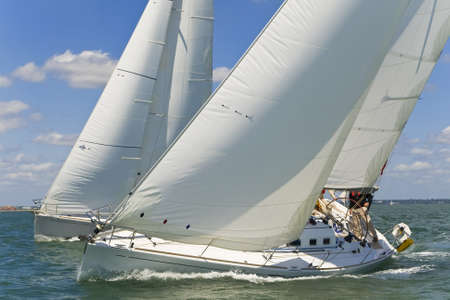Two beautiful white yachts racing close to each other on a bright sunny day Stock Photo